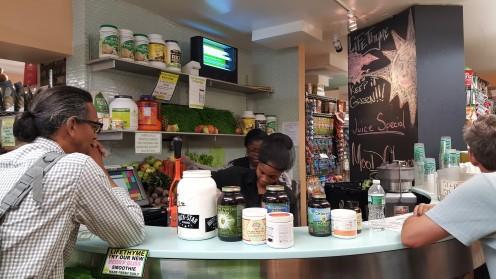 """Um bar de sucos feitos na hora permite que você escolha qualquer ingrediente do mercadinho, incluindo proteínas vegetais e ingredientes como grama de trigo (""""wheatgrass"""") Compartilhar"""
